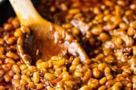 Stir a batch of cooked Southern Baked Beans with a wooden spoon in a large cast iron skillet.