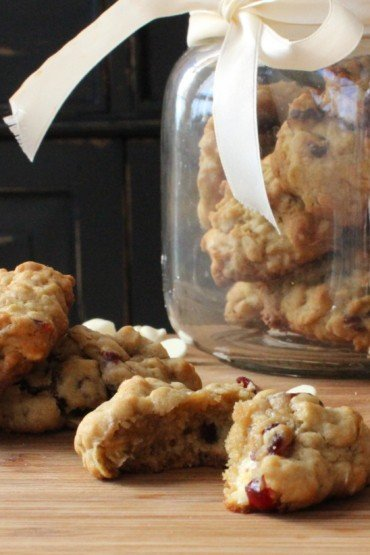 Oatmeal, Cranberry and White Chocolate Chunk Cookies on a wood cutting board next to a jar filled with cookies