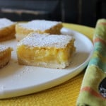 Lemon Squares on a white plate next to a patterned napkin with forks all sitting on a yellow place mat