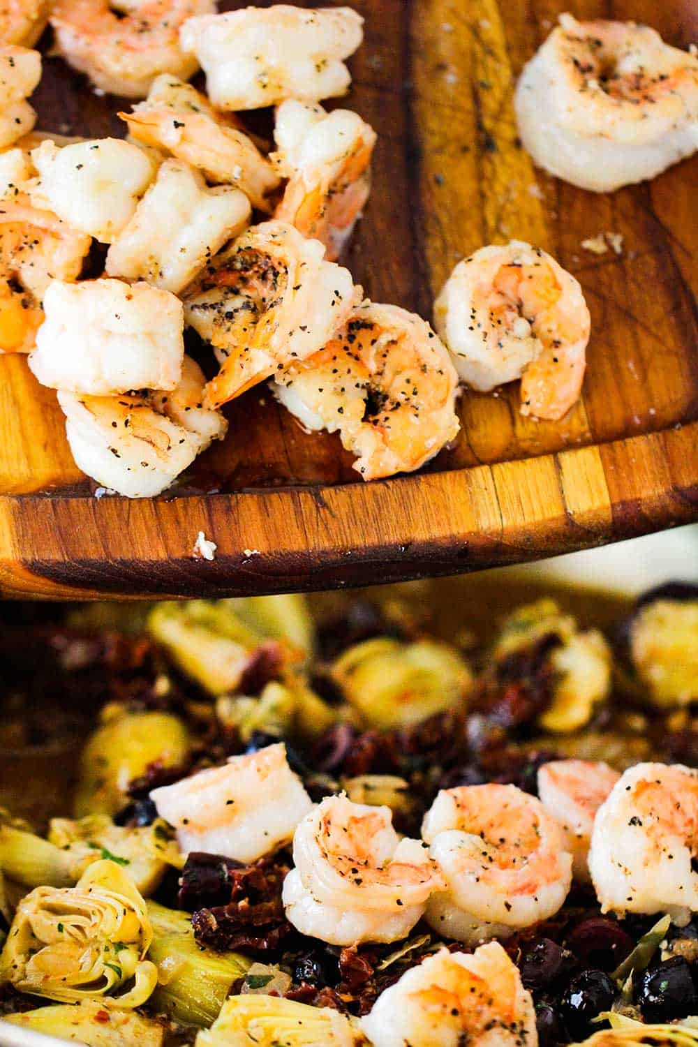 Seared shrimp falling from a wooden cutting board into a pan of cooked artichokes and olives.