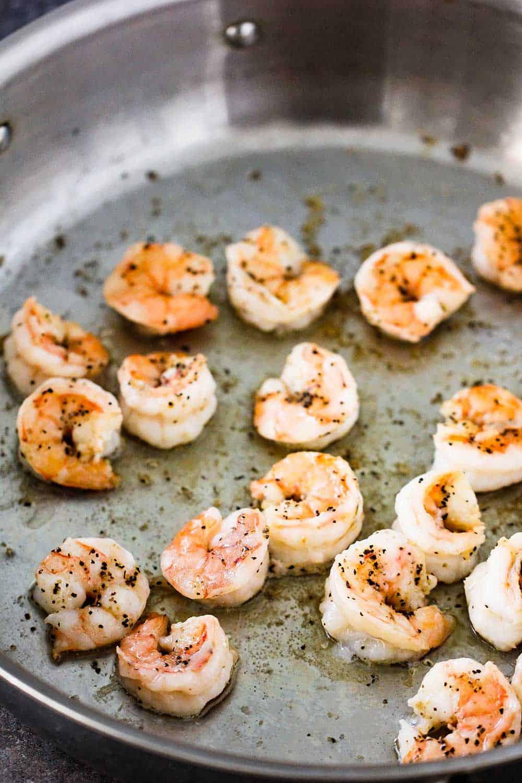 A large silver saucepan filled with sautéed shrimp.