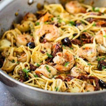 A large silver saucepan filled with Mediterranean pasta with shrimp.