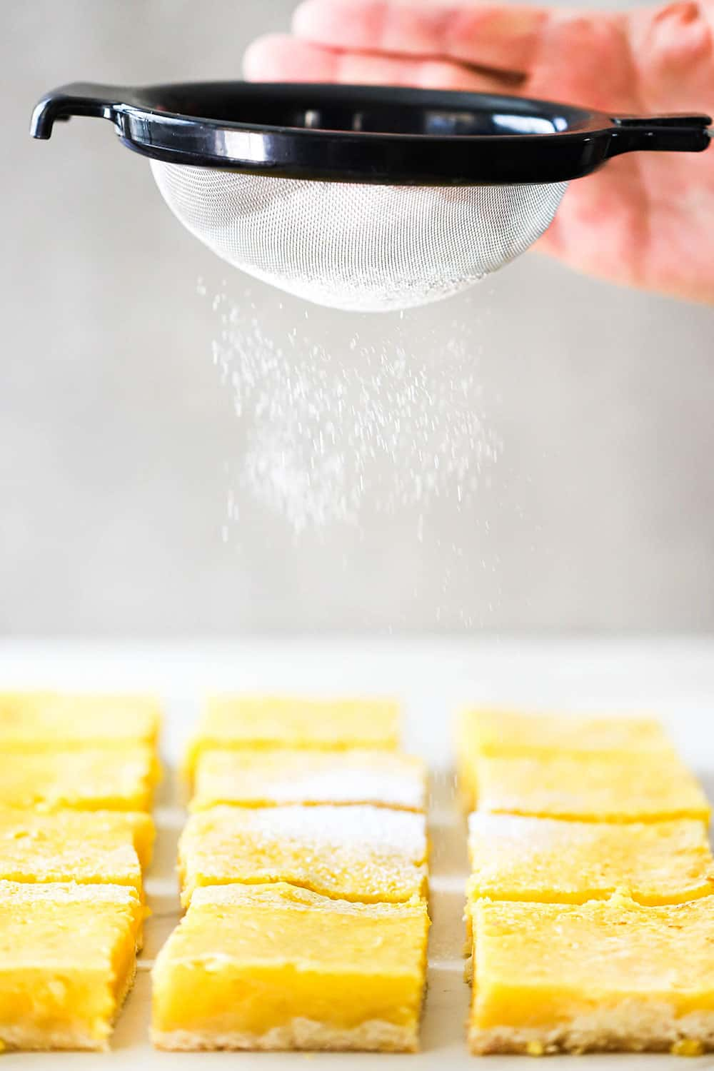 A hand using a small sieve to sprinkle powdered sugar over the tops of cut lemon bars.