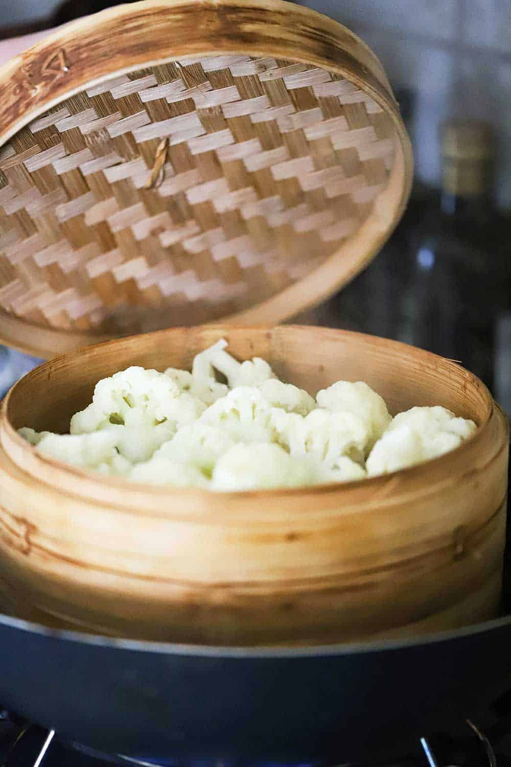 A lid of a bamboo steamer being lifted up to reveal cauliflower florets that have been steamed.