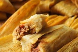 Homemade tamales with pork filling on a board in wrappers