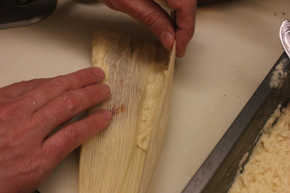Fold over the tamale from the right, and then the left