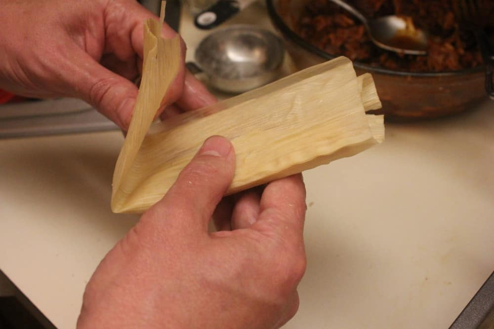 Fold the triangular bottom of the husk up
