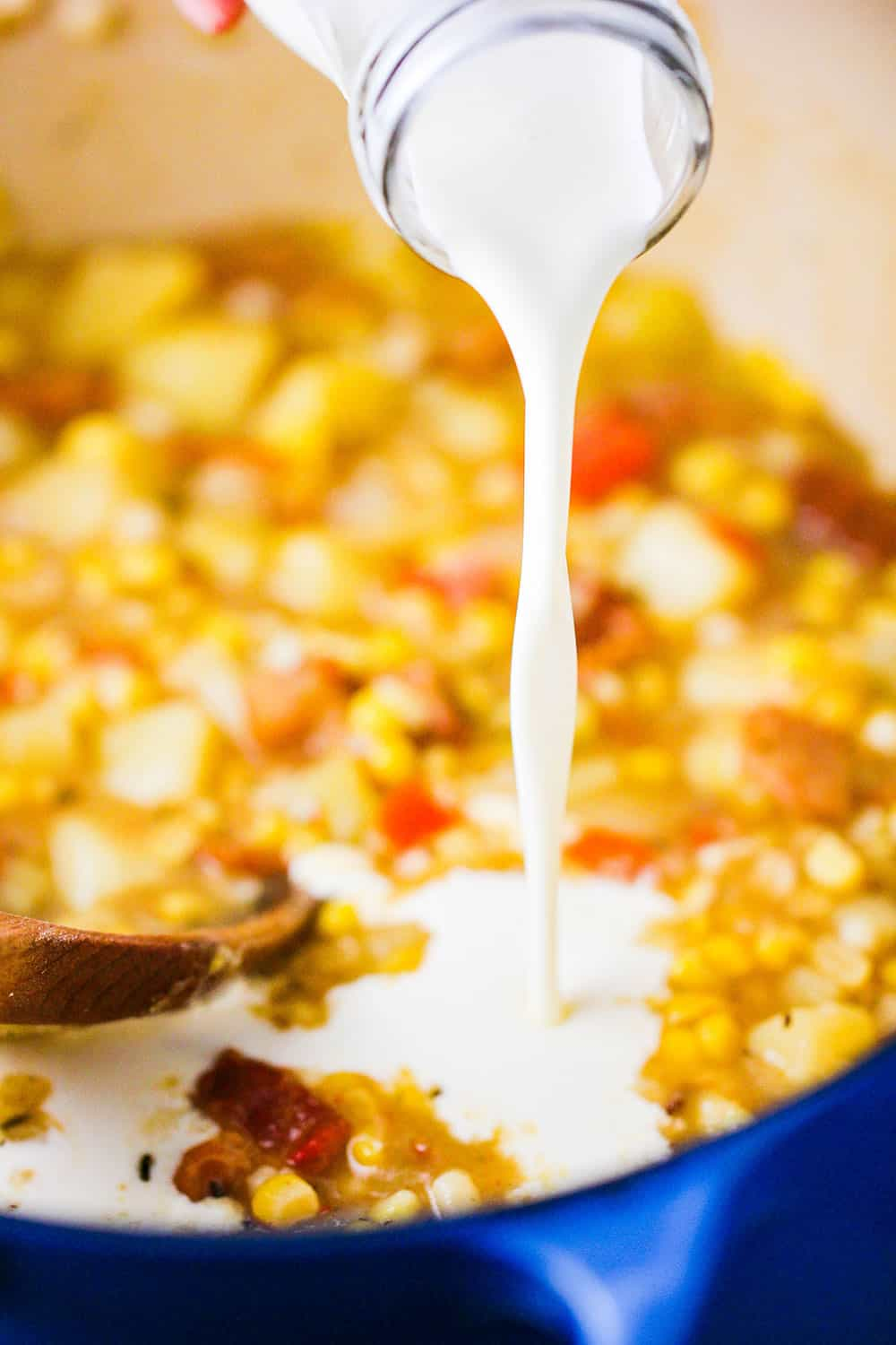 A dairy bottle of cream being poured into a large pot of farm fresh corn chowder.