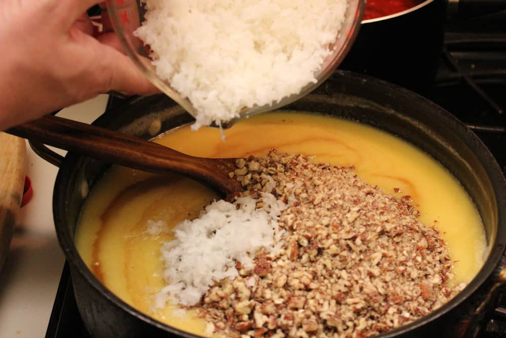 Shredded coconut, pecans and vanilla being added into a skillet of silky icing for German chocolate cake. to the mixture