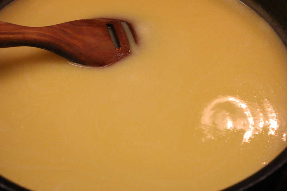 A large skillet filled with a silky icing mixture with a wooden spoon in it.