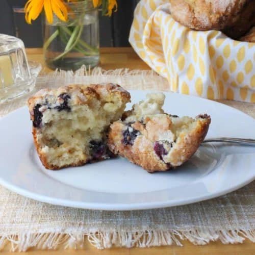 A white plate with a White Chocolate and Blueberry Muffin sitting on top of a beige place mat with a basket of muffins behind it