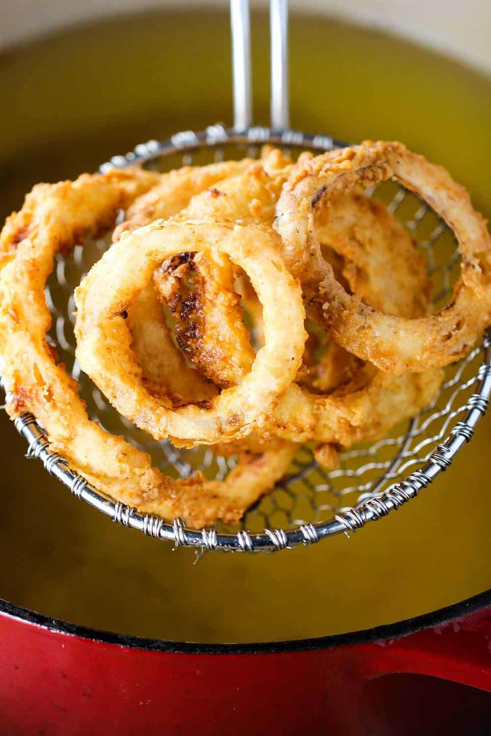 Onion rings being pulled from a deep fryer