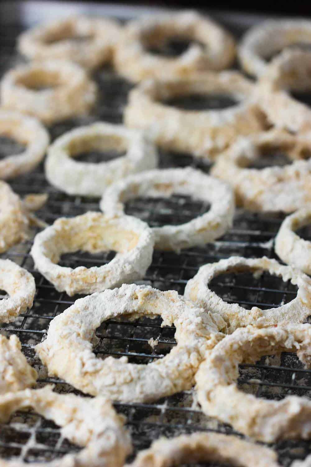 Breaded onion rings on a baking rack