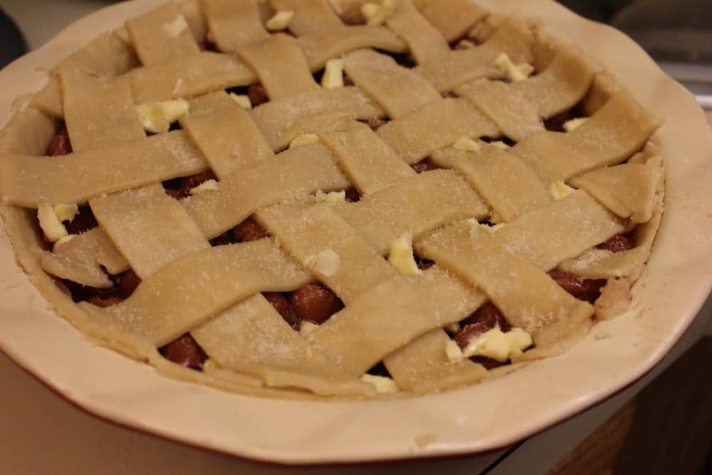 An overhead view of an uncooked cherry pie with a lattice pie dough topping.