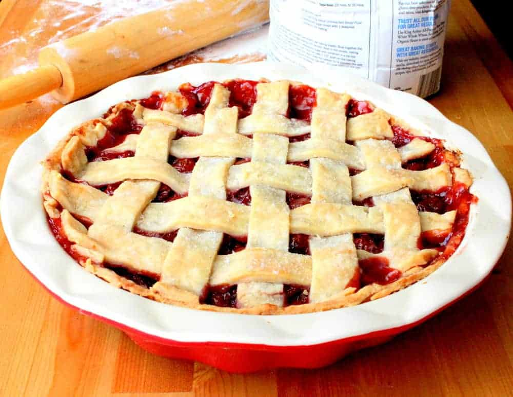 A homemade cherry pie in a red and white pie dish with a lattice top sitting next to a rolling pin