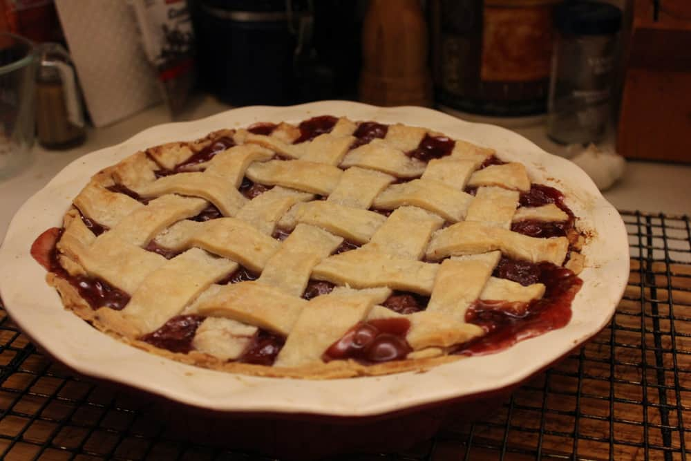 A cherry pie with a lattice crust topping fresh out of the oven on a wooden cutting board.