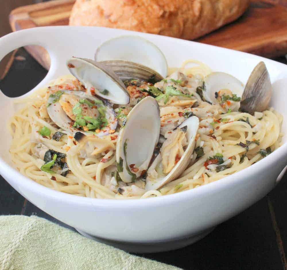 Pasta with White Clam Sauce in a large white bowl next to a cutting board with a loaf of bread