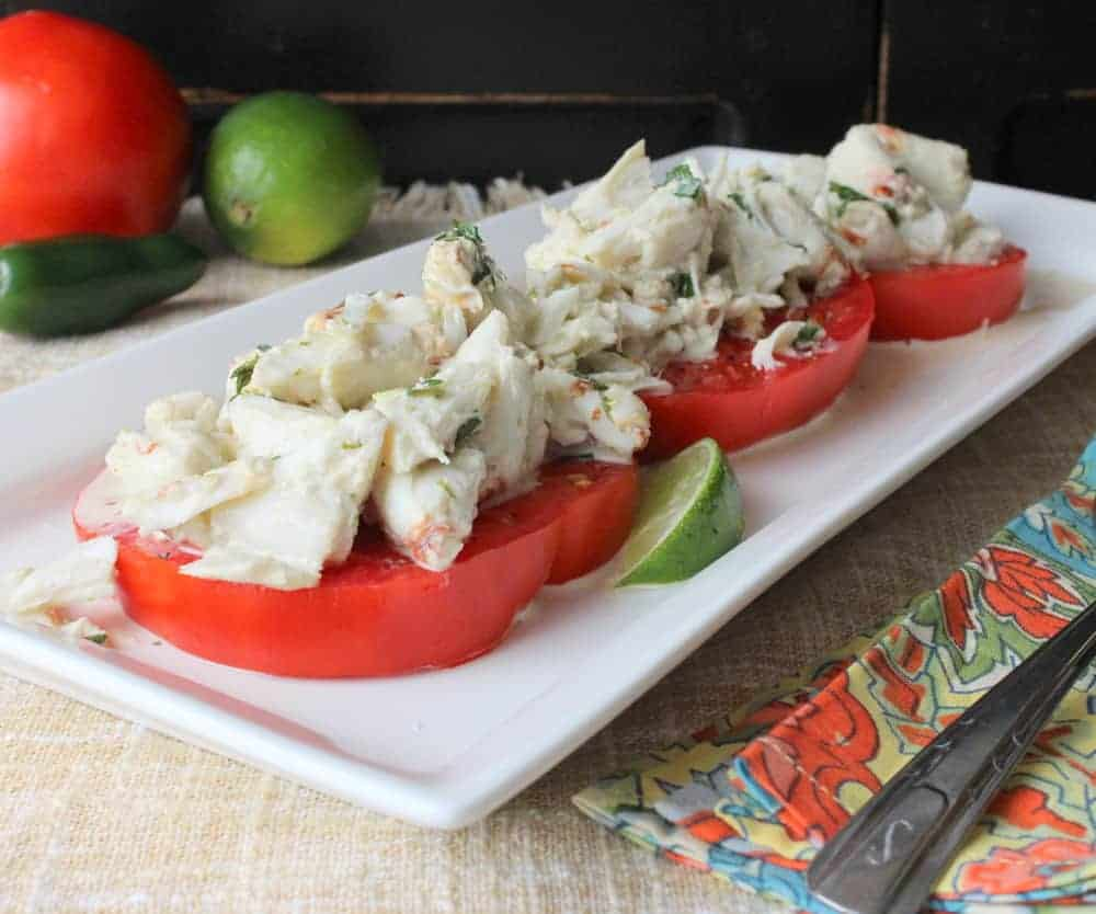 Lump Crab Tomato Salad on a white dish next to a patterned napkin with a fork