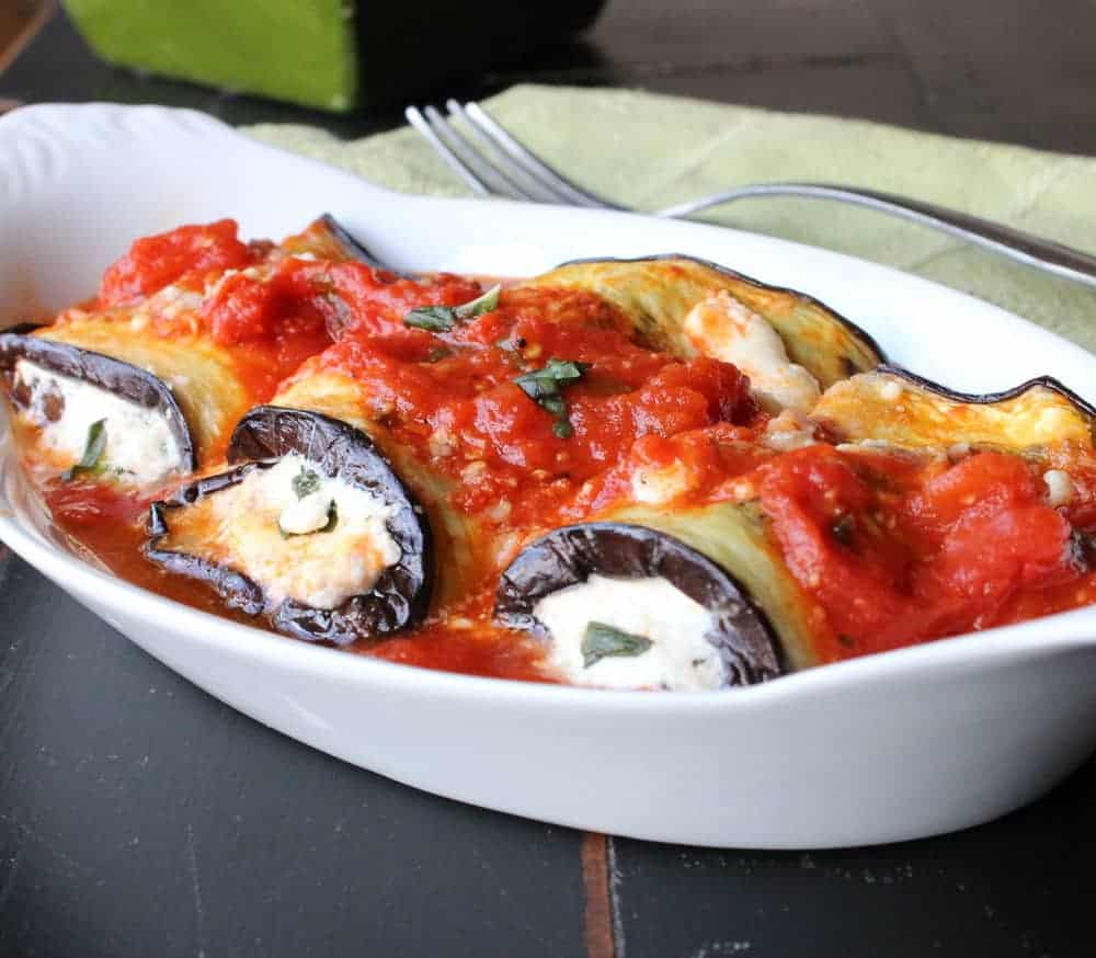 A white dish holding a serving of eggplant involtini.