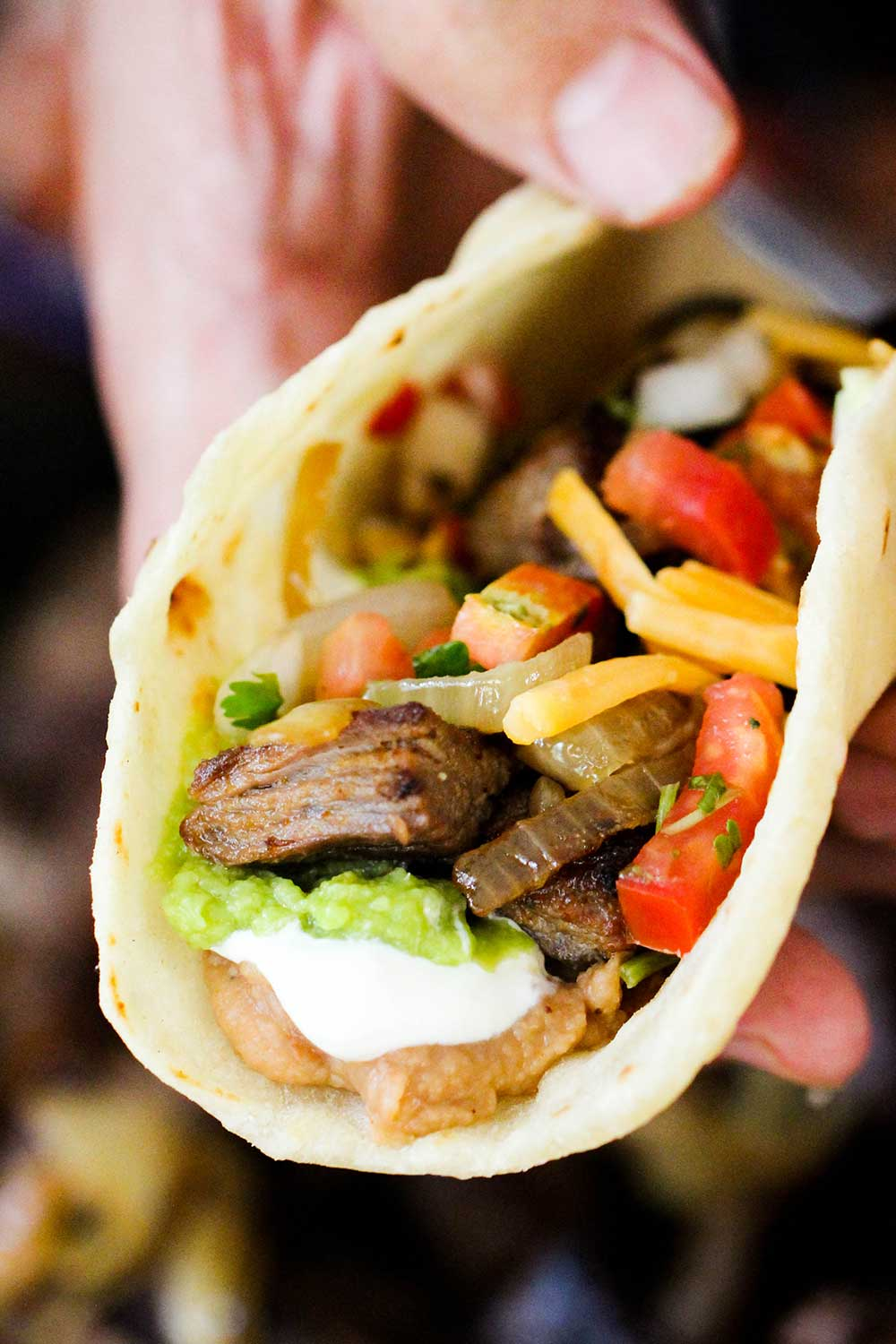 A hand holding an authentic steak fajita filled with beans, guacamole, sour cream, steak and pico de gallo.