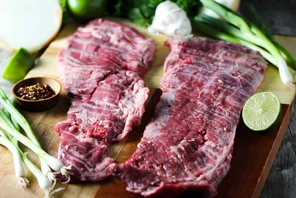Two large cuts of skirt steak on a butting board next to cut limes and scallions.