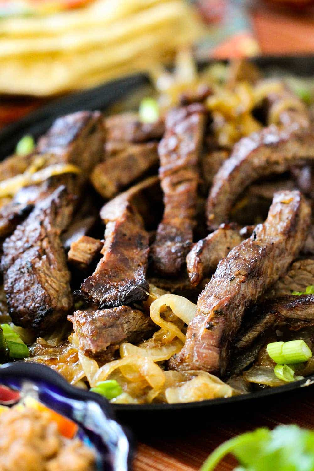 Steak fajitas on a bed of caramelized onions on a fajita pan.
