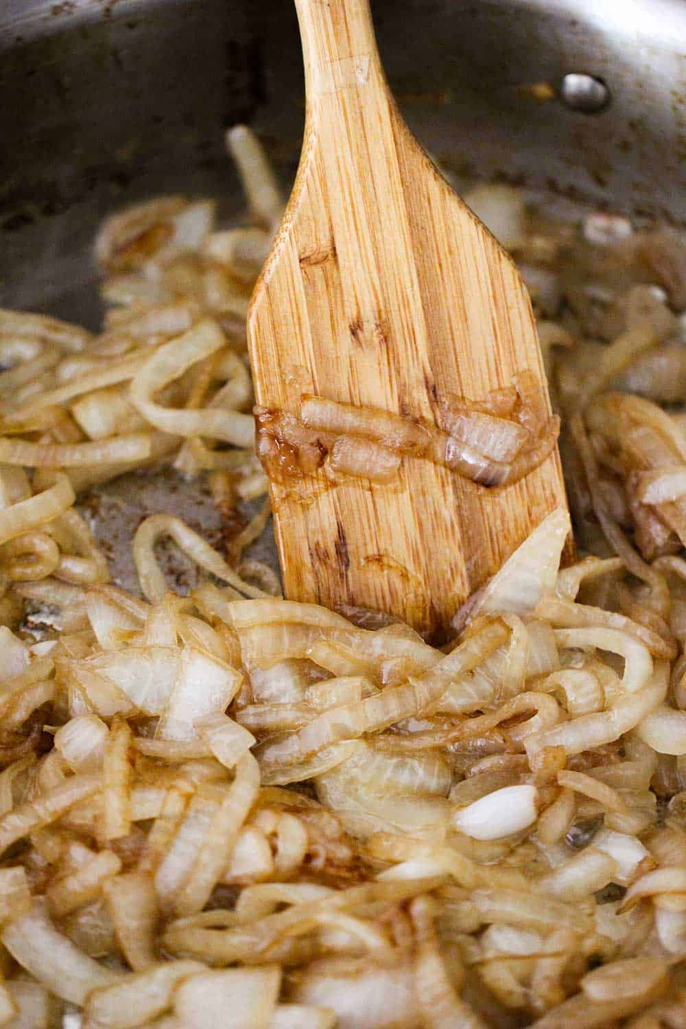 A large skillet with a wooden spoon stirring caramelized onions