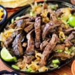 Authentic steak fajitas on a large fajita pan with sliced limes and scallions nearby.