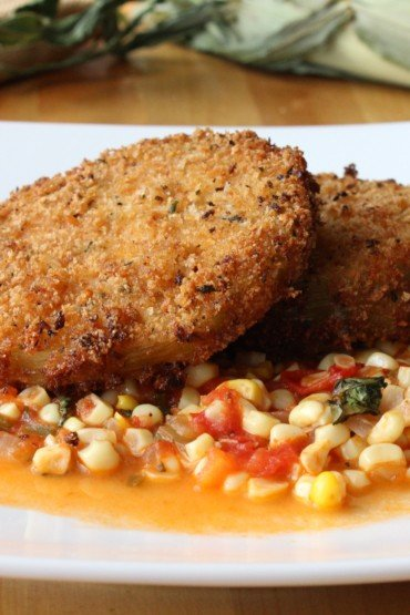 Two fried green tomatoes on a white plate filled with corn and tomato sauté