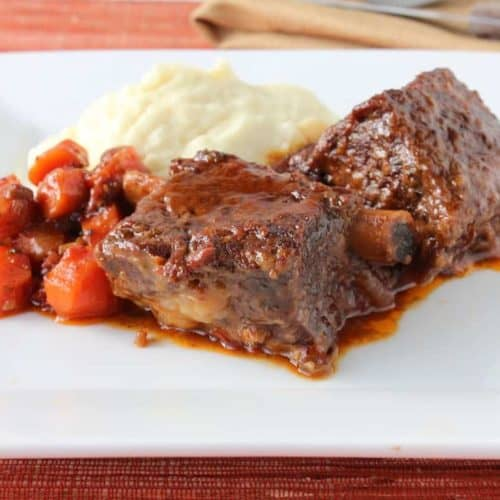 A white square plate of braised short ribs, carrots, and mashed potatoes.