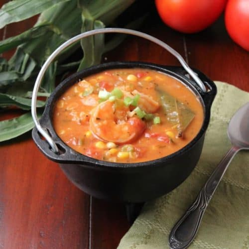 Shrimp, tomatoes, and corn stew next to a green napkin and spoon
