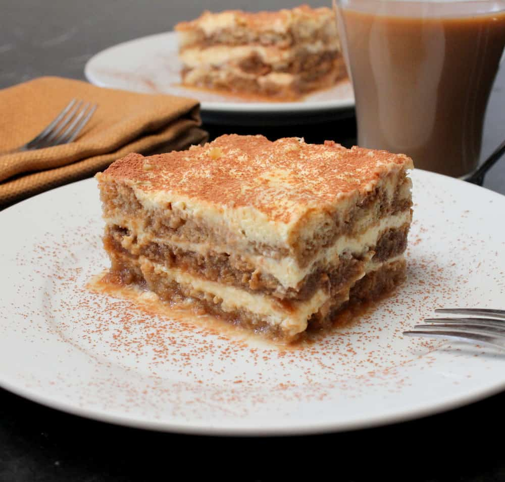 A white plate with a slice of classic tiramisu on it next to a cup of coffee.