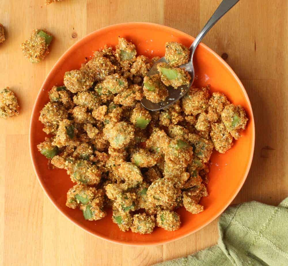 An orange bowl of Fried Okra with a silver spoon