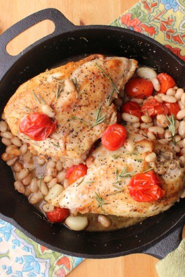 A large cast-iron skillSkillet-roasted chicken with tomatoes, white beans and wine sitting in a large cast-iron skillet next to festive napkins.