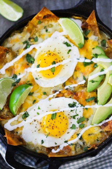 An overhead view of chilaquiles in a cast-iron skillet with 2 slices of lime and sliced avocado on top.