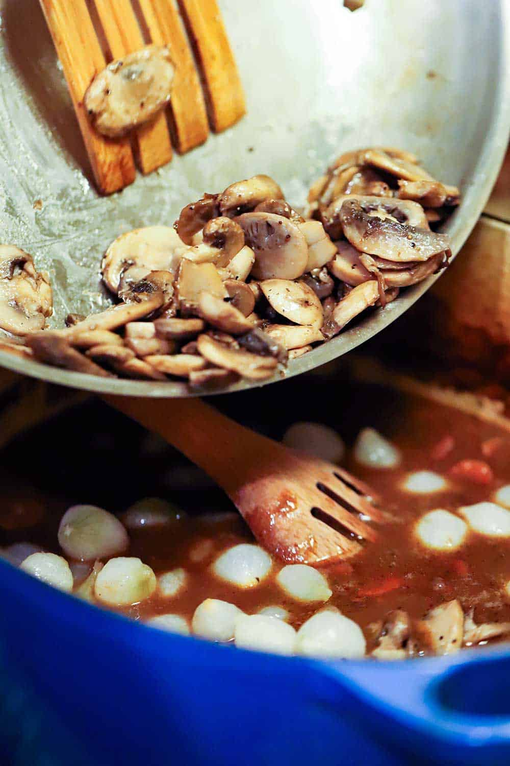 Sautéd mushrooms being transferred into a pot of simmering beef bourguignon.