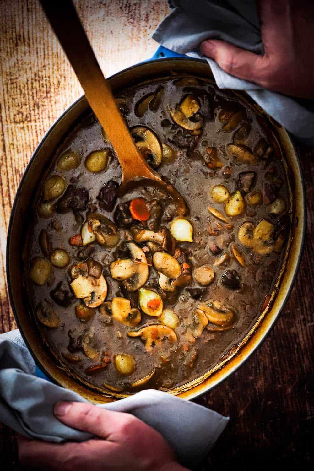 A large oval Dutch oven filled with beef bourguignon being held by two hands.