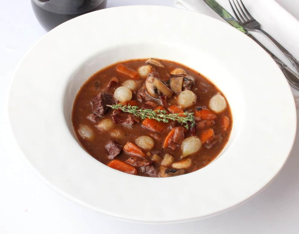 A white bowl with Beef Bouruignon
