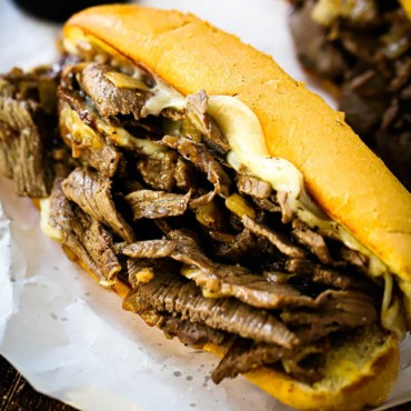 A large Philly cheesesteak loaded with sliced cooked ribeye and melted Provolone cheese sitting on white butcher paper.