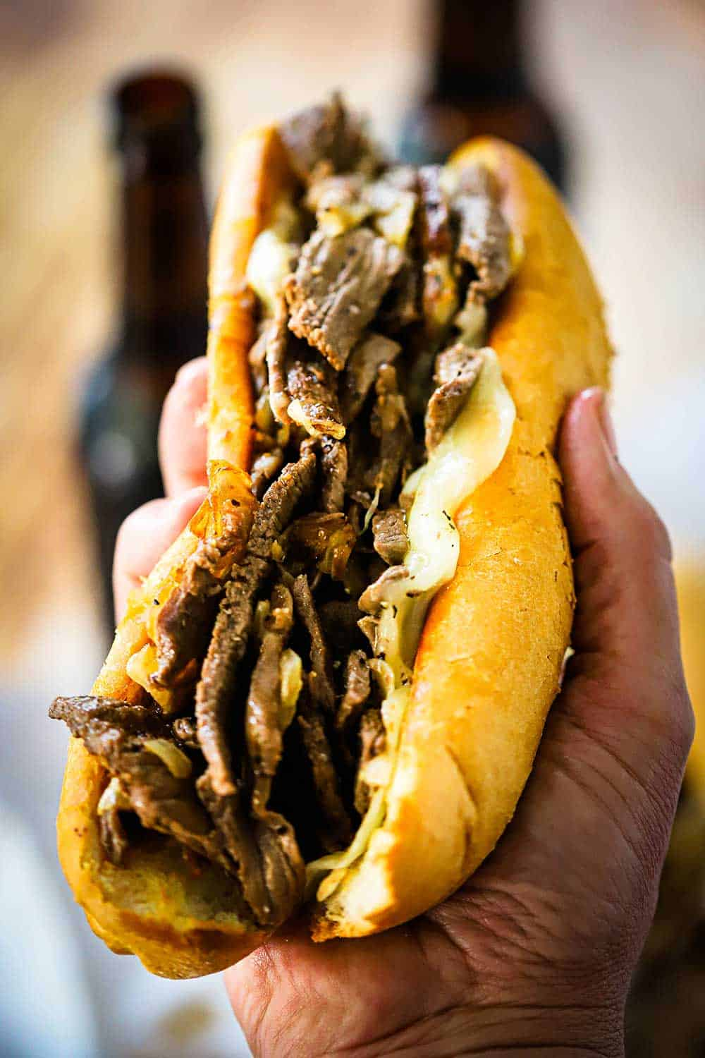 A hand holding up a Philly cheesesteak sandwich loaded with cooked ribeye slices, onions, and melty provolone cheese on a toasted hoagie bun.