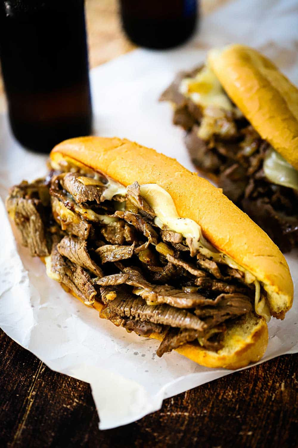 Two Philly cheesesteaks loaded with meat and cheese sitting on butcher paper next to two glasses of dark beer.