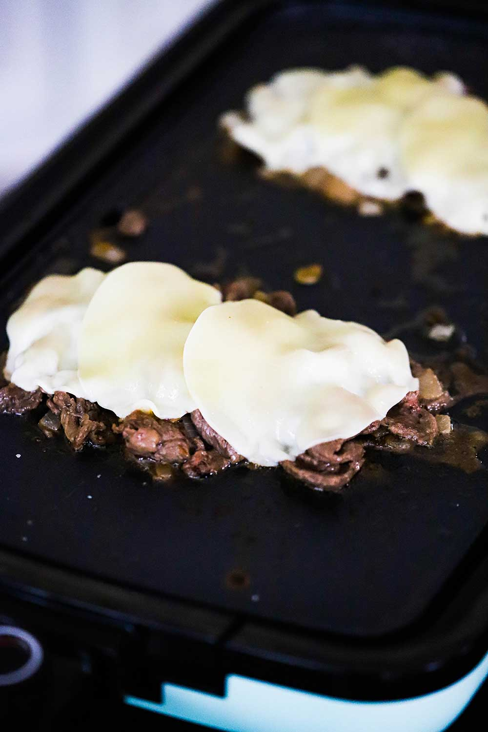 Two mounds of cooked sliced of ribeye steak on a hot griddle with Provolone cheese slices melting on top of each mound of meat.