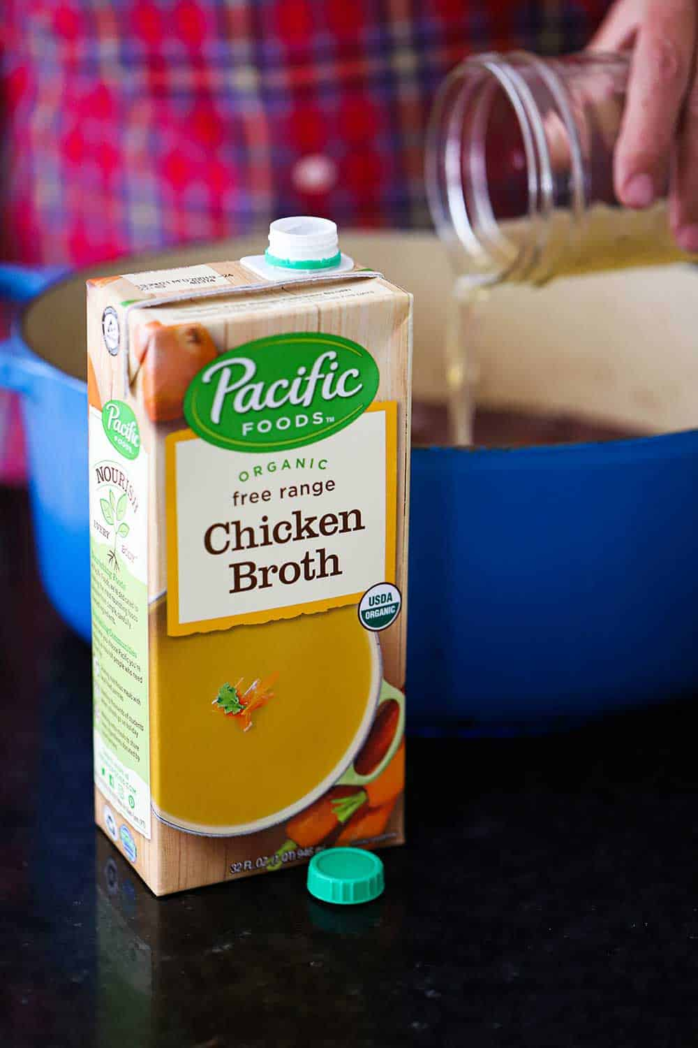 A box of Pacific Food Chicken Broth in front of a blue Dutch oven with a hand pouring broth from a jar into the pot.