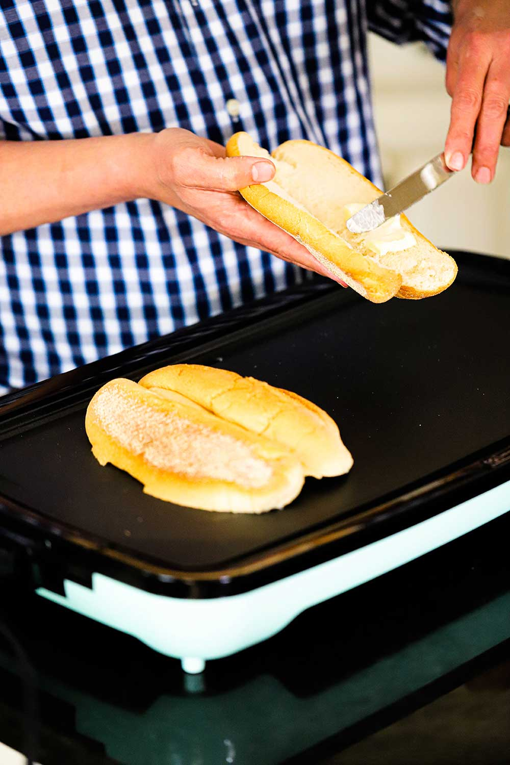 A person smearing softened butter onto the inside of a cut open hoagie over a griddle with another hoagies being toasted, cut-side down.