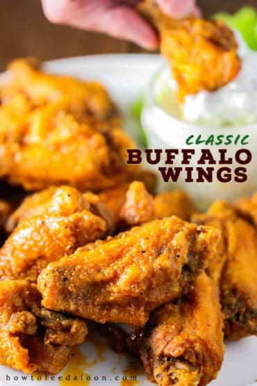 A close-up view of classic buffalo wings with a hand dipping a wing into a jar of blue dressing in the background.