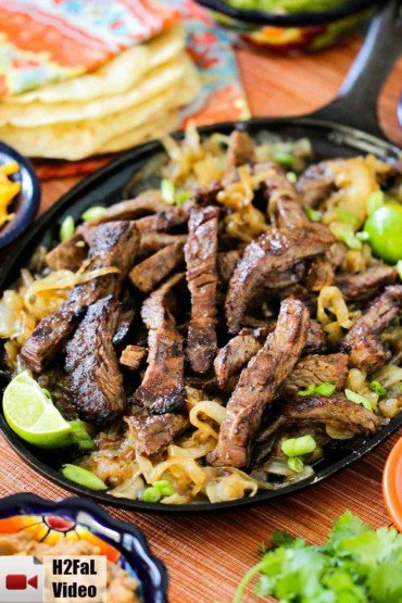 A cast iron fajita skillet of steak fajitas with limes and green onions nearby.