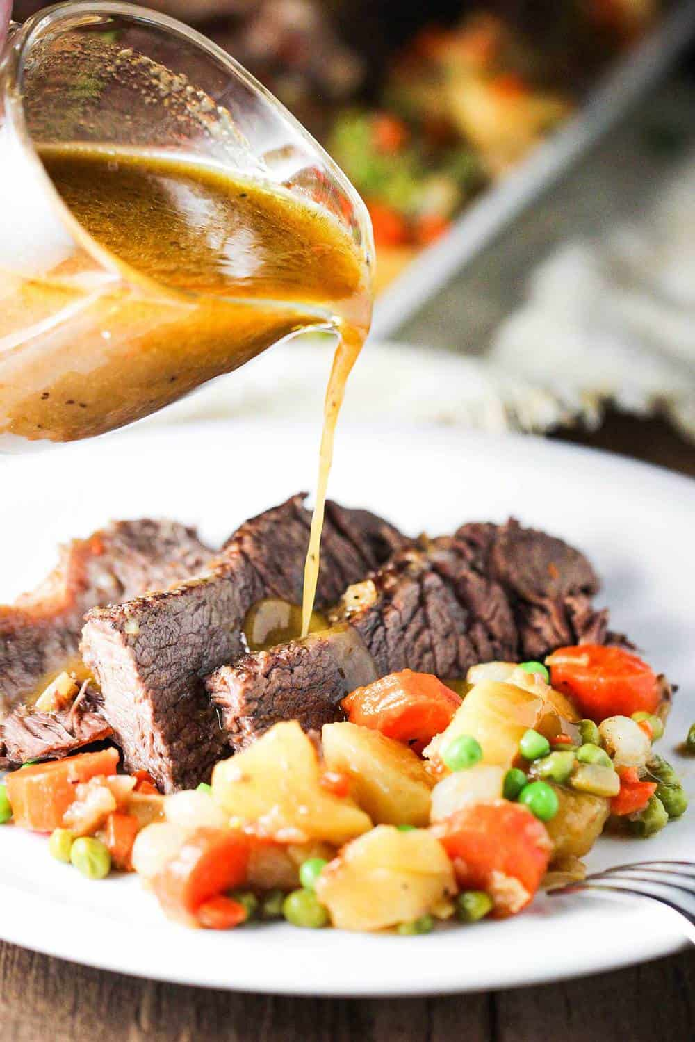 Gravy pouring onto a plate of American pot roast and vegetables