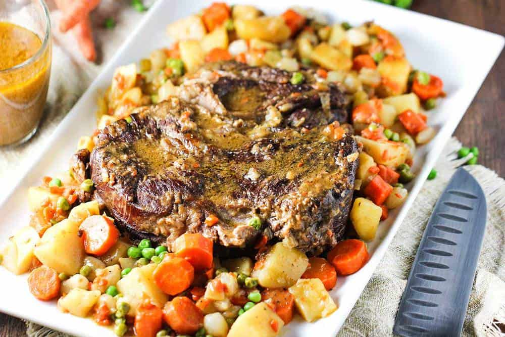 American pot roast with potatoes and carrots on a large white platter