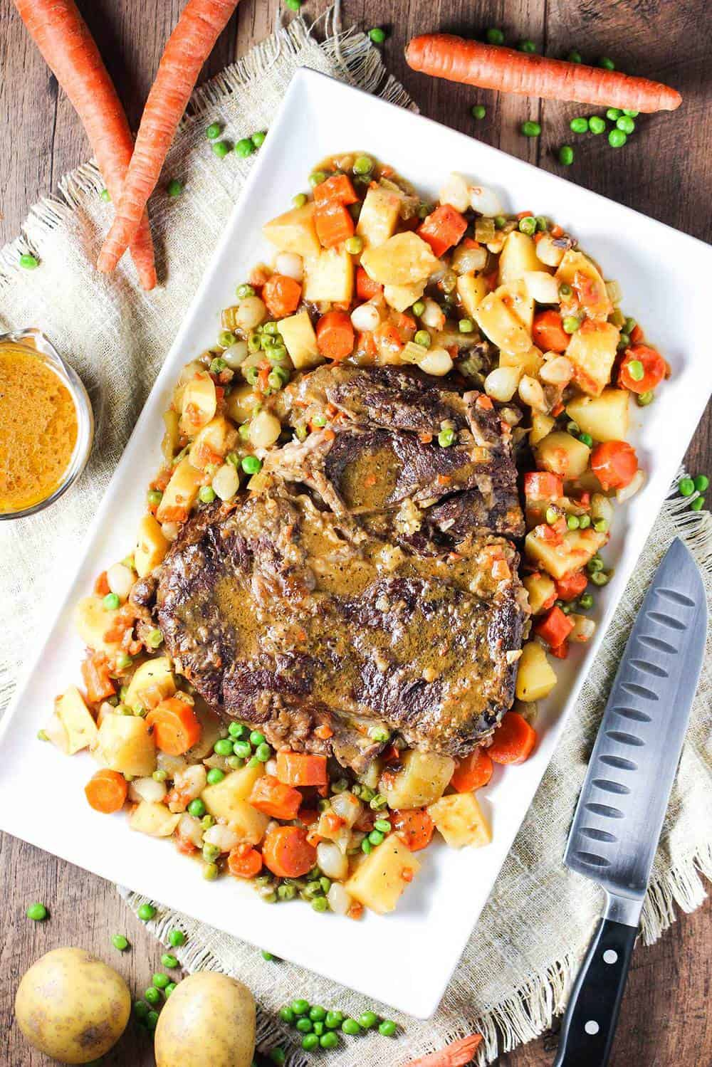 A large rectangular platter holding an American pot roast and vegetables