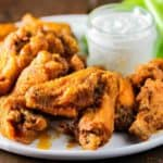 A round white platter of classic buffalo wings with a dish of blue cheese dressing and cut celery.
